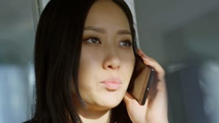 Closeup shot of young Asian lady standing in the office and speaking on mobile phone