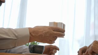 Closeup tracking shot of senior man giving a gift to his wife at restaurant table; elderly woman opening box and admiring present