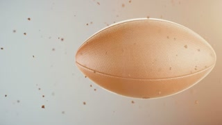 Computer animated sports background with leather football spinning and flying throw dust particles against blue background