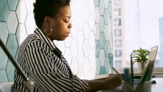 Concentrated african american woman typing on laptop while working at desk in the office
