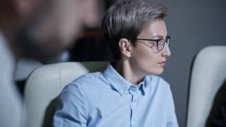 Concentrated businesswoman in eyeglasses looking at computer screen while working late in the dark office with colleagues