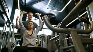 Concentrated woman trying to do seated overhead shoulder press with dumbbells, her instructor helping her
