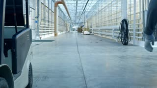 Crane shot of unrecognizable man in overalls walking along hall of large industrial greenhouse