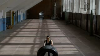 Crane shot with tilt down of strong young woman in fitness clothes pushing and flipping heavy tire in empty gym