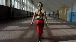 Crane shot with tilt up of fit sportswoman in fitness clothing doing handstand walk in empty gym