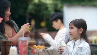 Cute Asian little girl sitting with ice cream at cafe table outdoors and posing while mother photographing her with smartphone