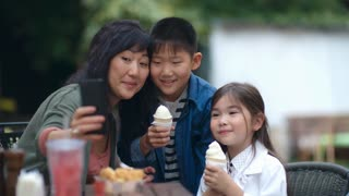 Cute little Asian boy and girl holding ice cream and smiling at smartphone camera while taking selfie with mother at cafe table outdoors
