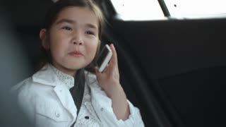 Cute little Asian girl riding in backseat in car and chatting on mobile phone