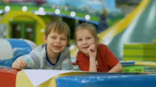 Cute little boy and girl lying on floor in children play center and smiling at camera when drawing picture together