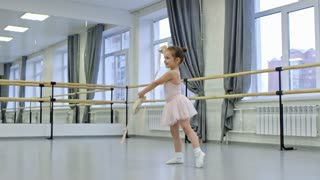 Cute little girl wearing tutu skirt and leotard holding ballet shoes in hands and spinning around in dance studio