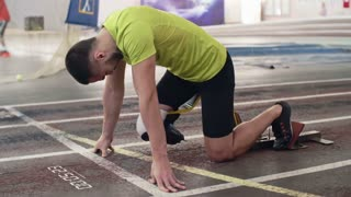 Determined athlete with prosthetic leg starting from blocks on indoor stadium track and running; heartbeat rate projected in the air and digitally animated countdown appearing on track