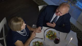 Directly above shot of senior woman and elderly man sitting before table and clinking glasses with wine, then drinking and chatting during date in restaurant
