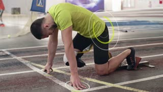 Disabled sportsman with prosthetic leg starting from blocks on indoor stadium track and running; pulse projected in the air and digitally animated countdown appearing on track