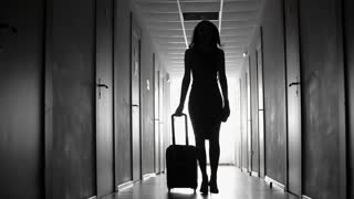 Dolly black and white shot of silhouette of elegant businesswoman with suitcase walking along hotel hallway