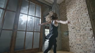 Dolly of happy young woman with curly hair dancing in empty loft