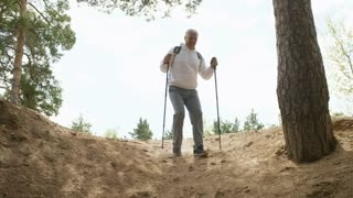 Dolly shot of elderly man with backpack and trekking poles running down steep mound in forest