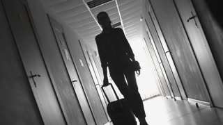 Dolly with flip shot of silhouette of businesswoman with suitcase and man talking on mobile phone walking along dark hallway of hotel