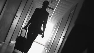 Dolly with flip shot of silhouette of female traveler with suitcase and man talking on mobile phone walking along dark hotel hallway