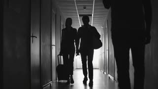 Dolly with slow motion of silhouette of female traveler with suitcase and her male partner walking along dark hallway of hotel towards man talking on mobile phone
