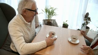 Elderly couple having romantic date in cafe: senior woman taking gift box from husband while having coffee