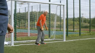 Elderly man in sports clothing and goalkeeper gloves standing at goal net and trying to catch football