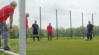 Elderly man in sports clothing standing at goal net and catching football while playing with group of friends outdoors on warm summer day, slow motion