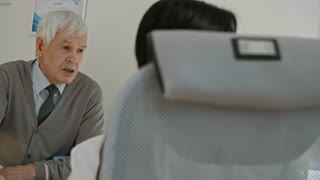 Elderly man sitting at desk in doctor's office and talking to female specialist while she working with x-ray image and writing down prescription
