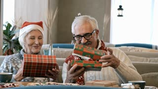 Elderly wife and husband celebrating Christmas in restaurant: they smiling, opening gift boxes and admiring surprises