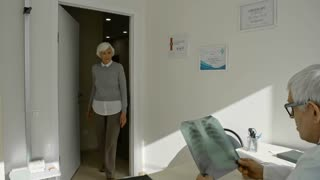 Elderly woman walking into doctor's office and talking to senior practitioner while he examining x-ray Image