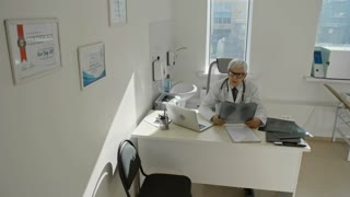 Elderly woman walking into doctor's office, sitting and listening to senior practitioner while he showing x-ray image and explaining diagnose