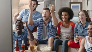 Emotional sports fans sitting on couch and watching live game on TV. They shouting with raised hands for their team in slow motion