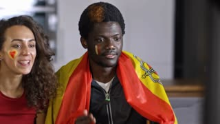 Excited African man holding flag of Spain, yelling and embracing his girlfriend while watching soccer on TV at home