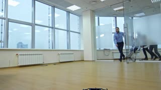Excited colleagues pushing chair with businesswoman into new empty office, laughing and having fun after moving in new business center