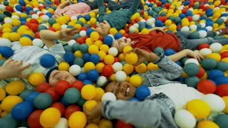 Excited multi ethnic children of primary school age smiling and laughing when playing with colorful hollow plastic balls in ball pit of indoor playground