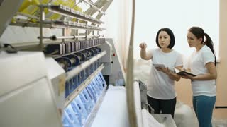 Experienced female technician using digital tablet and explaining young colleague how to operate industrial textile machine at factory
