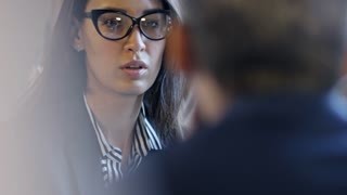 Face of serious young businesswoman in glasses listening to unrecognizable colleague seen from their back when discussing agreement details at business lunch