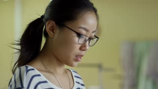 Face of young Asian woman in glasses discussing clothing design with client and showing samples of fabric and color swatches to them