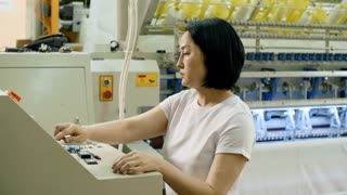 Female Asian technician pressing buttons on computer while turning on industrial textile machine at plant and then looking at camera and smiling