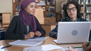 Female teacher explaining something on laptop screen to young middle eastern woman in hijab during lesson in school for migrants