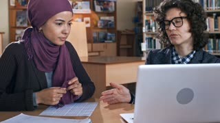 Female teacher in eyeglasses explaining something on laptop screen to young muslim woman in hijab during lesson in school for migrants