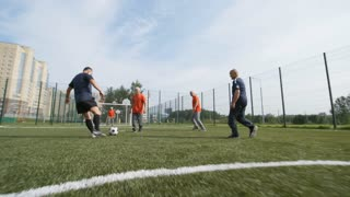 Follow shot of group of elderly people running towards goal net while playing football, one of them kicking ball and scoring goal