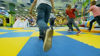 Follow shot of group of multi ethnic children of primary school age running towards inflatable mountain in playroom and climbing it