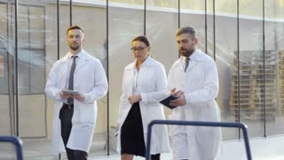 Follow shot of three engineers in lab coats, two men and one woman, inspecting industrial greenhouse complex
