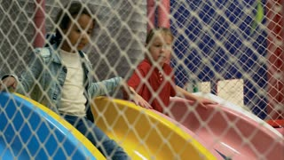 Follow shot of two little multi ethnic girls having fun in playroom together and sliding down into ball pit