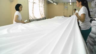 Following shot of Asian female coworkers covering table with white fabric while working in team at textile manufacturing plant