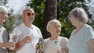 Four elderly people standing together and talking to each other in park while drinking water from bottles