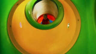 Front view of amazed little girl of primary school age having fun walking through play tunnel in indoor amusement park