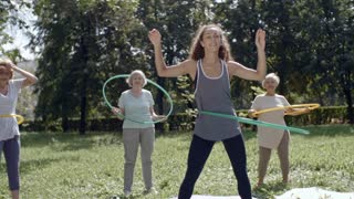 Front view of elderly women with their trainer doing hula hoop exercises in park on warm summer day and smiling