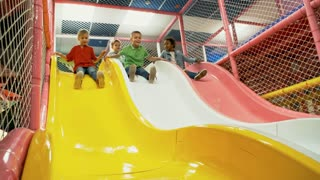 Front view of four multi ethnic children of primary school age sliding into ball pit when having fun together in playroom