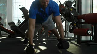 Front view of mature man performing plank row with dumbbells at the gym